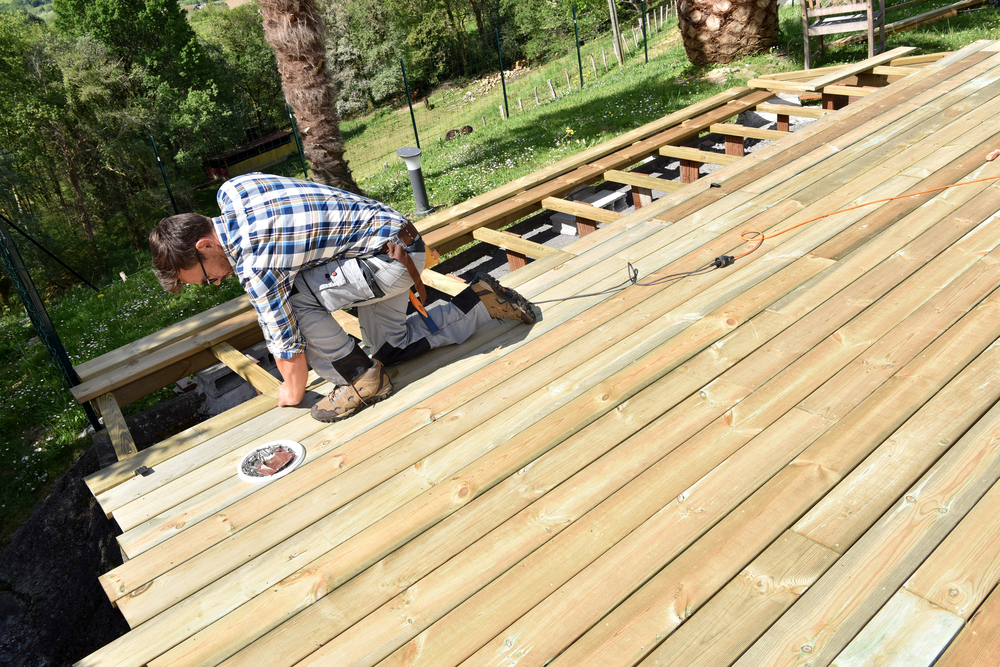 A worker laying a timber deck